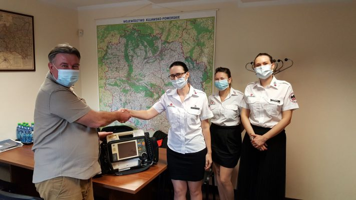 Dyrektor Krzysztof Tadrzak przekazuje defibrylator przedstawicielkom PCK w Bydgoszczy